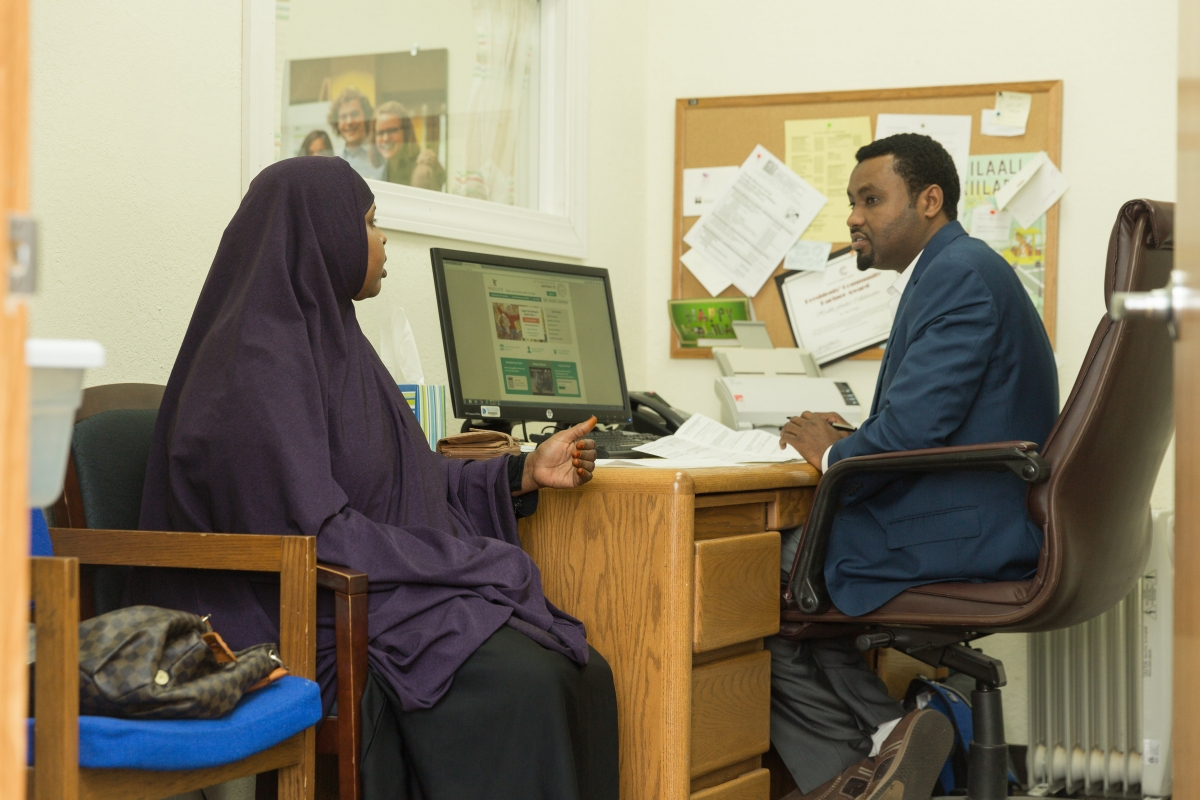 Ali Hassan, Patient Advocate and MNsure navigator, helping a client through the MNsure application process at the HealthFinders clinic in Faribault.